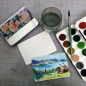 The tin of papers, watercolors, brush, etc.